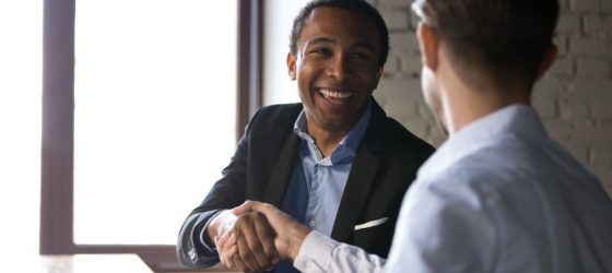 seller shakes hands with buyer after learning how to sell your business to a competitor