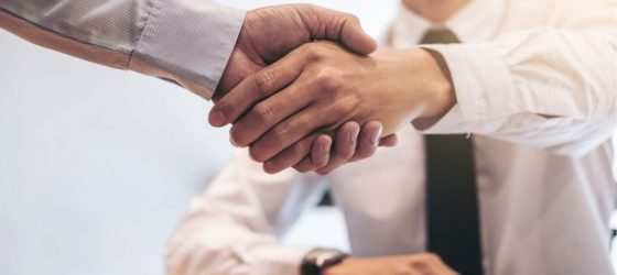 business men shake hands after running through important questions to ask when buying a business